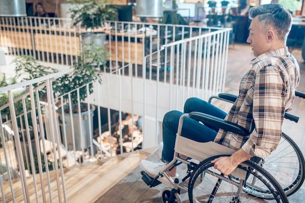 할 수 없음. 휠체어를 탄 겁에 질린 외로운 남자가 방에 있는 계단 앞에서 멈추는 프로필