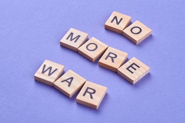 폭력과 전쟁의 용납 불가. 슬로건 더 이상 나무 조각에 글자로 쓰여진 전쟁. 파란색 배경에 고립.