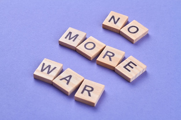 Inadmissibility of violence and war. slogan no more war written with letters on wooden cubes. isolated on blue background.