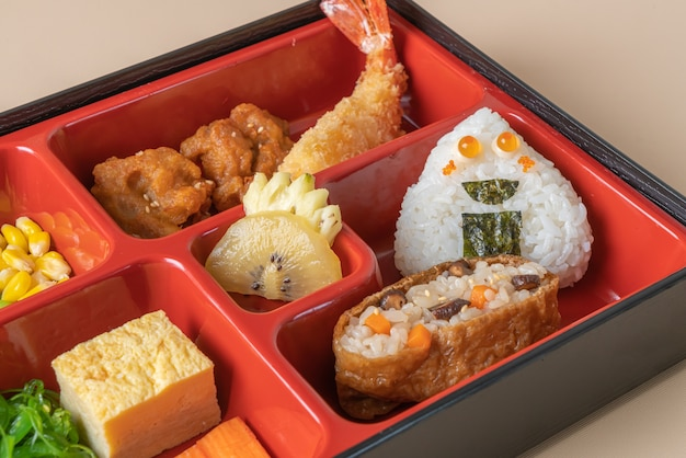 (inari sushi) sushi rice wrapped in dried tofu with fried shrimp and fried chicken in bento set - japanese food style