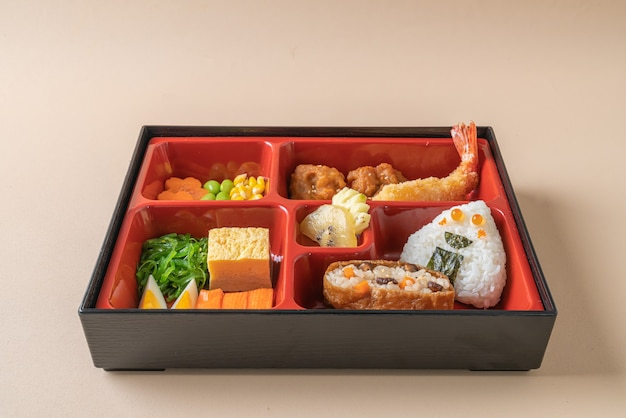 (inari sushi) sushi rice wrapped in dried tofu with fried shrimp and fried chicken in bento set