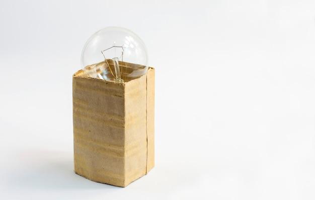 Лампа накаливания в коробке, на белом фоне, изолировать