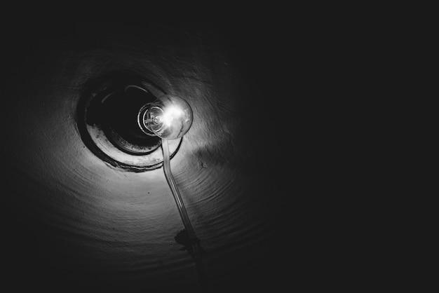 暗い部屋のクローズアップ内で白熱灯が燃えます。イルミネーション。粗い壁に古い電球。ランプは地下をグレースケールで照らします。暗闇の中で光。シンプルなモノクロ背景。コピースペース。