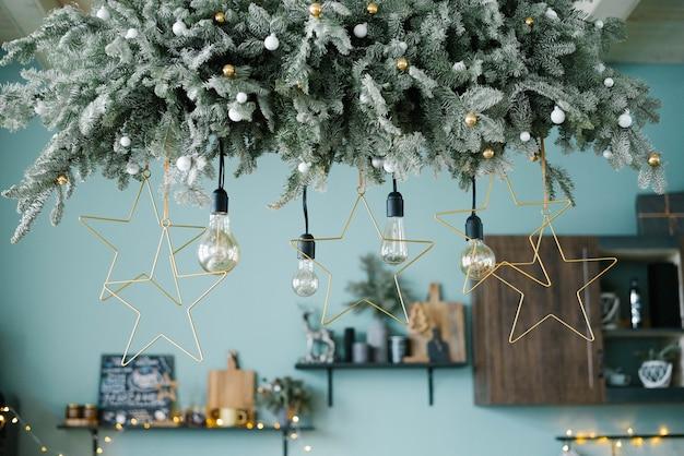 Лампы накаливания среди новогодней гирлянды на кухне, украшенной к рождеству
