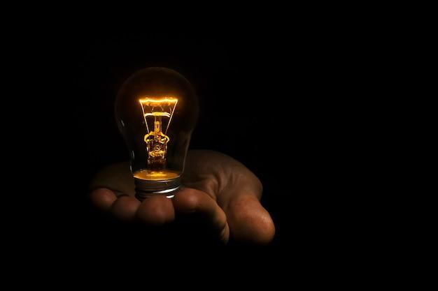 黒の背景の手に白熱電球