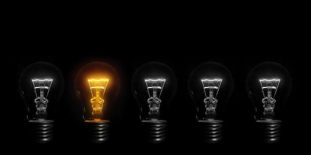 Лампа накаливания на черном фоне концепция выбора и уникальность
