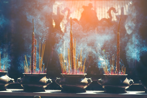 Incense burner sticks on joss stick pot are burning and smoke use for pay respect to the b