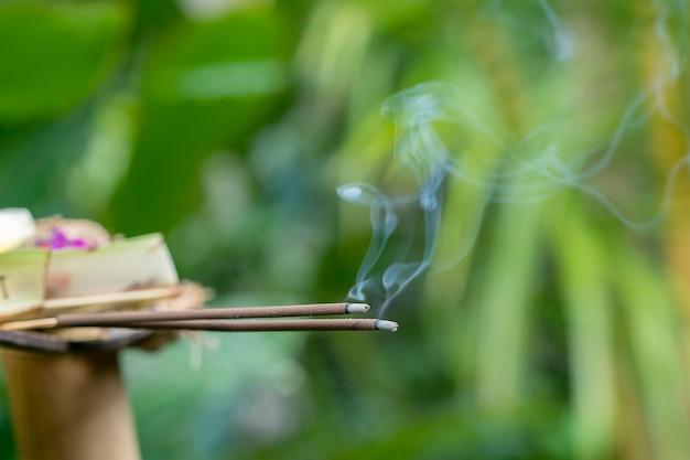 인도네시아 발리 섬 우붓의 중앙 거리에서 발리 힌두교 제물 의식을 위해 연기로 향을 피우고 있습니다. 확대