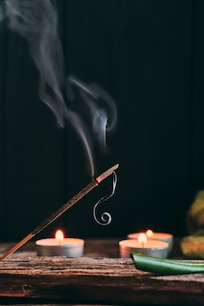 Incense stick and candles on rustic wood