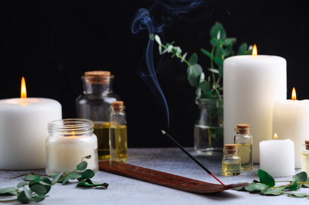 Incense stick with smoke on stone with white candles and essential oils