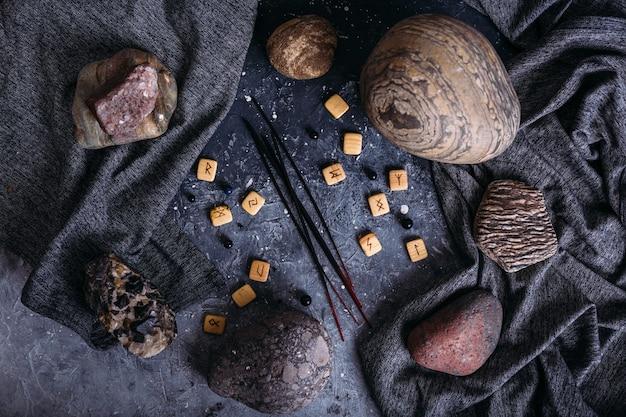 Ароматические палочки среди мрачной и эзотерической атрибутики, рунных камней. Premium Фотографии
