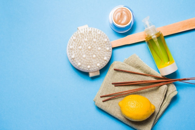 Incense sticks, lemon, body oil, natural homemade scrub in a jar and brush for dry massage on a blue surface