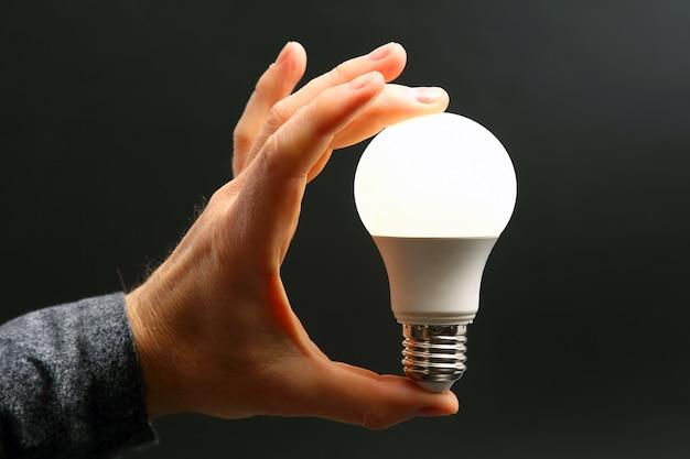 어두운 배경에 인간의 손에 led 새 램프가 포함되어 있습니다. 전기 산업.