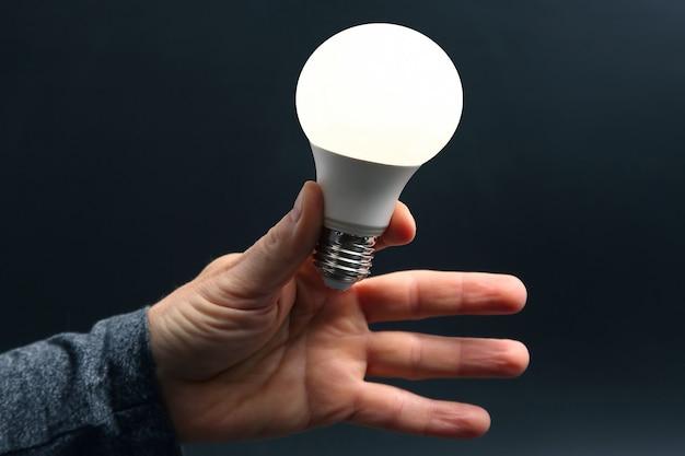 В комплекте новая светодиодная лампа в человеческой руке на темноте