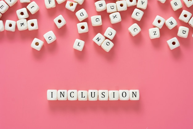 Inclusion text made from wooden cubes on pink table. inclusive social concept. flat lay.