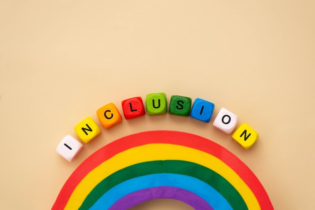 Inclusion word, colorful wooden cubes. inclusive social concept, tolerance and acceptance, flat lay.