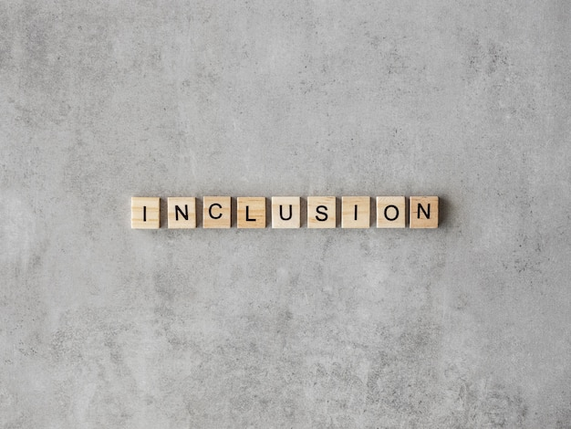 Inclusion word written in scrabble letters on marble background