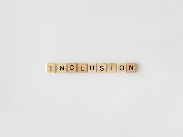 Inclusion word written in scrabble letters on white background