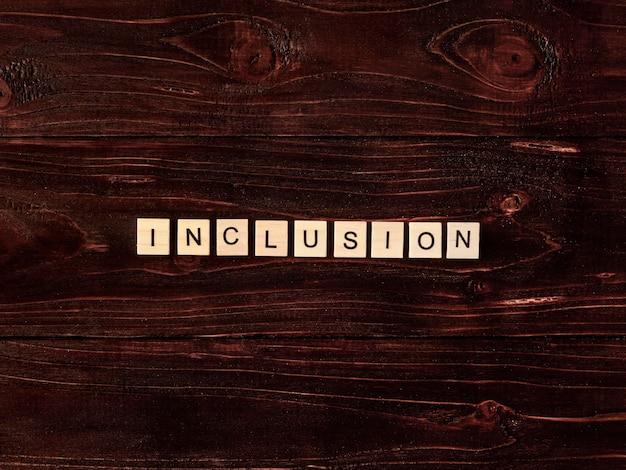 Parola di inclusione scritta in lettere di scrabble su fondo in legno