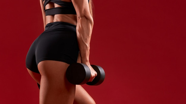 Incognito fitnesswoman holding dumbbell.
