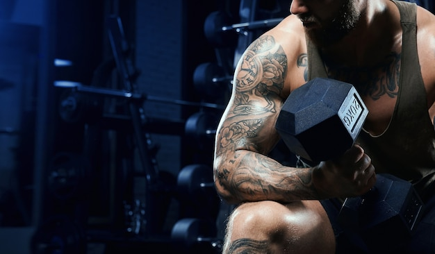 Incognito male bodybuilder training biceps with dumbbell.
