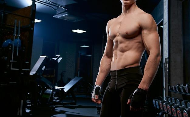 Sportivo senza camicia in incognito che posa in palestra.