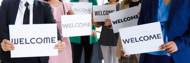 Инкогнито неопознанная неузнаваемая безликая группа женщин-сотрудников отдела кадров в бизнесе носит стоя, держа приветственный бумажный картонный знак, демонстрирующий теплое приветствие для нового сотрудника.
