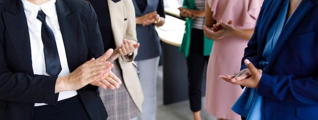 Инкогнито неопознанная неузнаваемая безликая группа офисных сотрудников женского пола в бизнесе носит стоячие аплодисменты и аплодирует, празднуя теплое приветствие для продвижения нового менеджера по службе.