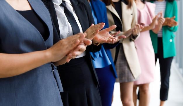 Инкогнито неопознанная до неузнаваемости безликая группа женщин-офисных сотрудников в бизнесе носит стоячие аплодисменты, бок о бок хлопая в ладоши, празднуя продвижение по службе коллеги в конференц-зале компании.