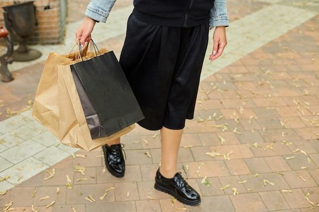 Женщина в режиме инкогнито, держащая несколько бумажных пакетов, гуляет на свежем воздухе в парке