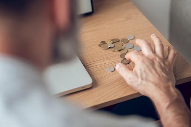 所得。テーブルの上のコインを計算している男の写真をクローズアップ