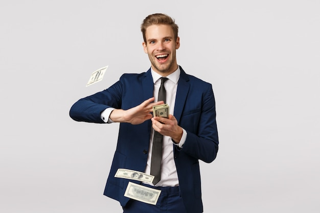Income, finance and success concept. wealthy, rich businessman signed big deal with company and celebrating, holding money, throwing cash at air and smiling