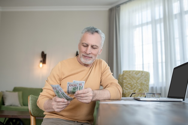 Income. gray-haired man standing and counting money