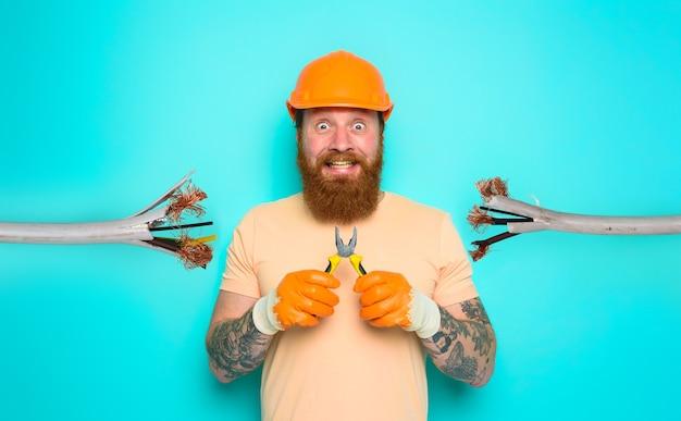 無能な労働者の電気技師は彼の仕事のシアンの背景について確信が持てない Premium写真