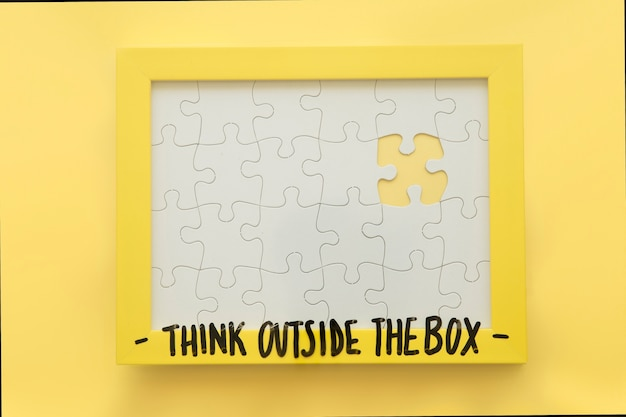 Incomplete jigsaw puzzle frame with think outside the box message