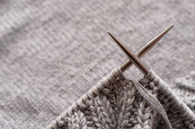Incomplete knitting project with metal needles close-up. knitting a gray wool sweater. the concept of hobby, creativity, needlework, handmade