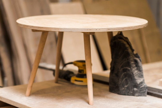 Incomplete small round wooden table on workbench