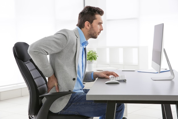 姿勢の概念が正しくありません。オフィスのテーブルに座っている男