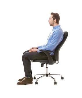 姿勢の概念が正しくありません。白で隔離の椅子に座っている男