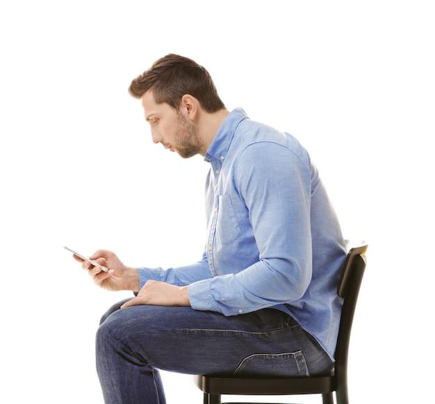 姿勢の概念が正しくありません。白で隔離の椅子に座っている電話を持つ男
