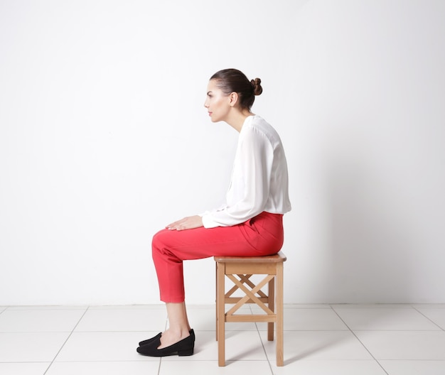 잘못된 자세 개념입니다. 흰 벽 배경에 의자에 앉아 있는 젊은 여성