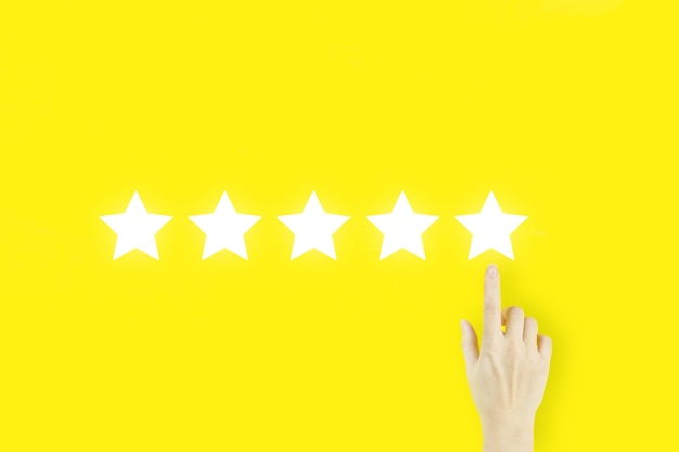 Increase rating evaluation and classification concept. customer experience concept. young woman's hand finger pointing with hologram five stars on yellow background.