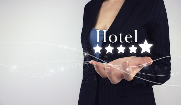 Increase rating evaluation and classification concept. hand hold digital hologram stars and inscription hotel on grey background. customer satisfaction