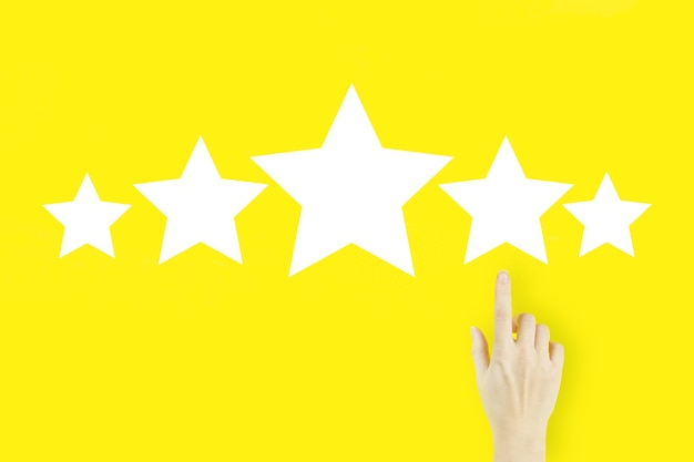 Increase rating evaluation and classification conceptyoung woman's hand finger pointing with hologram five stars on yellow background.