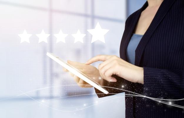 등급 또는 순위, 평가 및 분류 개념을 높입니다. 디지털 홀로그램 5개의 별이 있는 손으로 터치하는 흰색 태블릿은 흐릿한 배경에 표시됩니다. 사업 만족도 조사.