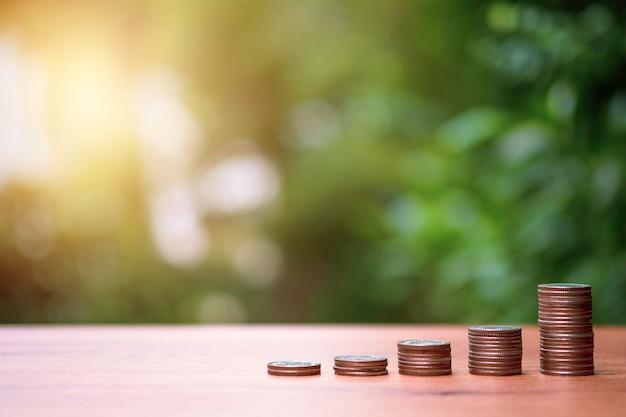 Увеличить график тренда монет, укладывающихся с ростом деревьев на фоне зелени. дивиденды и прибыль от концепции сбережений и инвестиций.