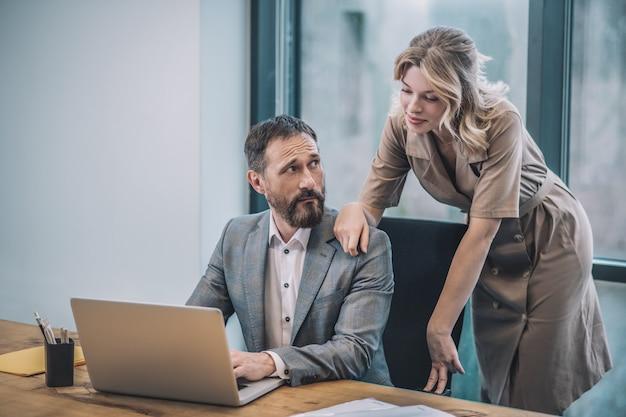 注目が高まった。近くに立っている金髪のきれいな女性がオフィスで彼の肩に触れているのを見てラップトップで驚いたビジネスマン