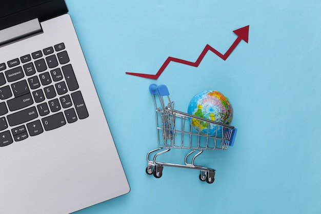 Increased global shopping. laptop, supermarket trolley with globe, growth arrow tending upwards on blue.