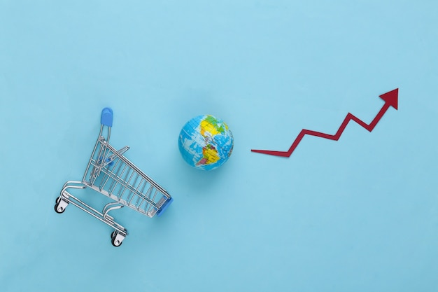 Increased global shopping. supermarket trolley with a globe, growth arrow tending upwards on blue.