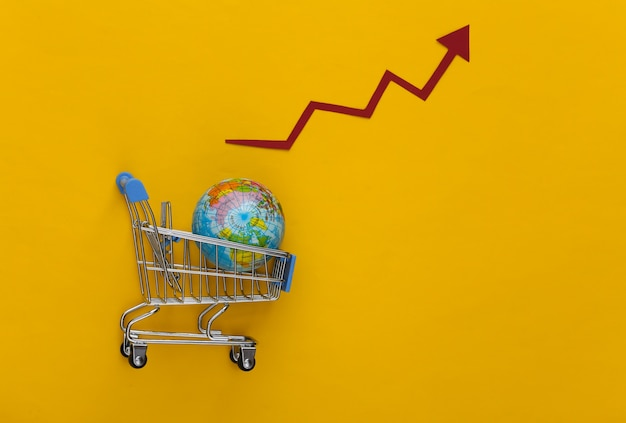 Increased global shopping. supermarket trolley with a globe, growth arrow tending upwards on a yellow.